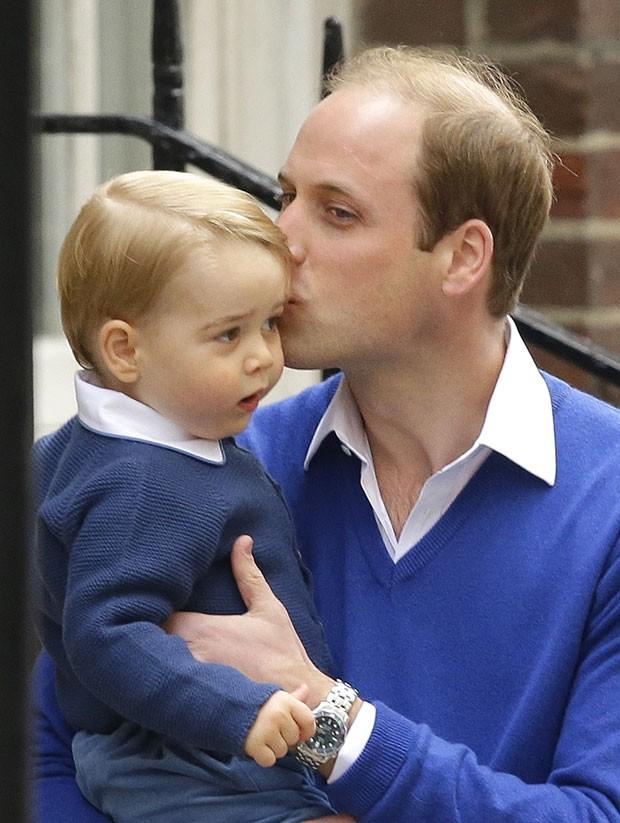 O príncipe William beija seu filho, o príncipe George, ao chegar ao hospital onde sua mulher Kate deu à luz a irmã do menino neste sábado (Foto: Matt Dunham/AP)