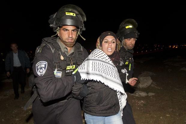 Agentes da polícia israelense retiram mulher do acampamento (Foto: Ahmad Gharabli/AFP)