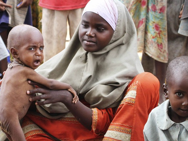 Mulher é vista cuidado de filhos desnutridos em Dadaab. Pessoas doentes não precisam jejuar durante o Ramadã, mas a maioria dos acampados que sofrem com a fome na Somália parece determinada a manter as tradições (Foto: Omar Faruk/Reuters)