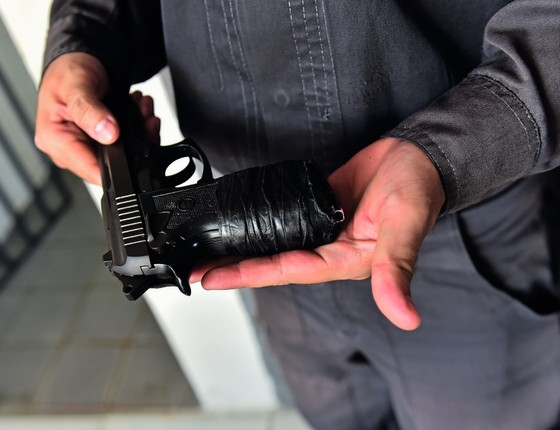 PM envolve sua arma quebrada com fita isolante em Natal.Categoria entrou em greve por atraso dos salários (Foto:  OSEMAR GONCALVES/ÉPOCA)