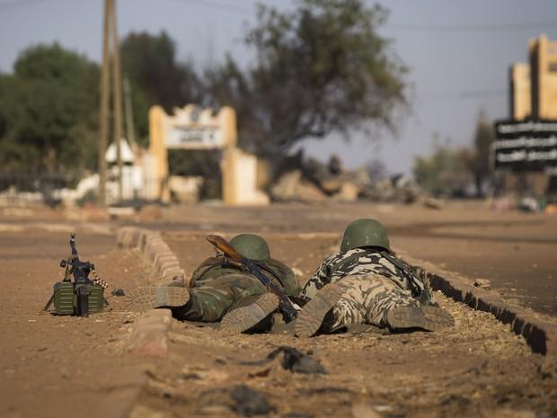 Soldados do Mali deitados no chão após ataques de carros-bomba nesta sexta-feira (22) (Foto: AFP PHOTO / Joel Saget)