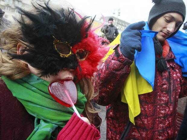 Mulher mascarada chupa pirulito em forma de coração durante protesto em Kiev (Foto: Gleb Garanich/Reuters)