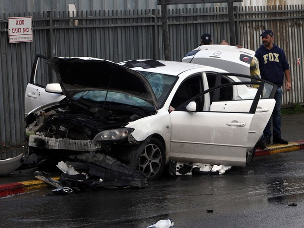 Polícia israelense examina carro utilizado em ataque palestino em Jerusalém nesta segunda-feira (14) (Foto: Mahmoud Illean/AP)