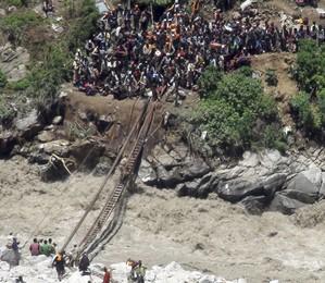 Polícia ajuda peregrinos a atravessarem um riacho atingido pelas fortes enchentes em Govind Ghati, na Índia. Estima-se que mais de 500 pessoas morreram em decorrência dos deslizamentos de terra e enchentes no país  (Foto: AP Photo)
