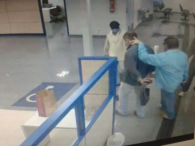 Imagem de câmera de segurança mostra bandidos fazendo homem de refém (Foto: TV Globo/ Reprodução)