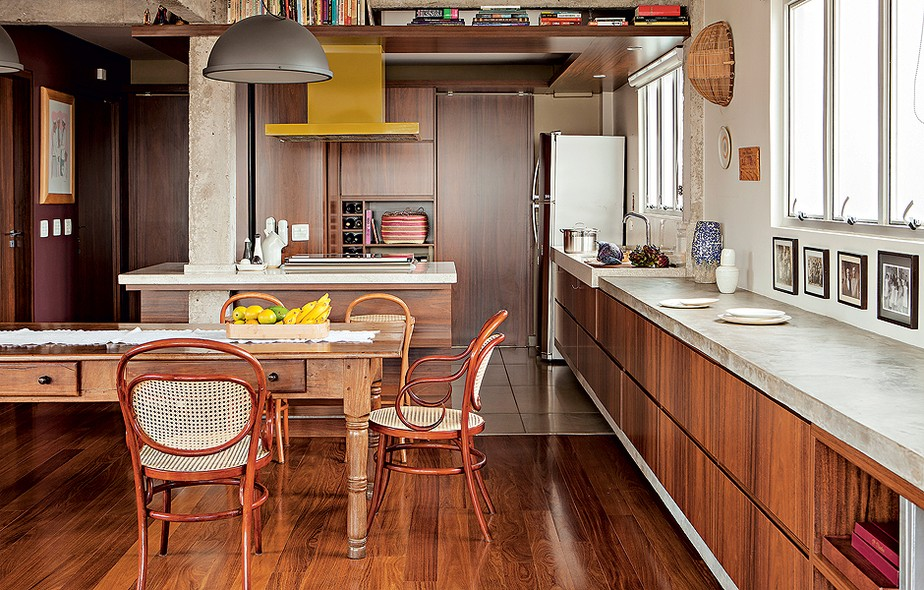 O projeto do arquiteto Gustavo Calazans tem cozinha escancarada, sem nenhum divisória com o resto da casa. A mesa de jantar é de madeira escura, semelhante aos móveis embutidos