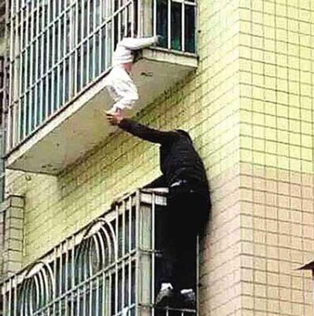 Criança ficou pendurada pela cabeça em grade da varanda de apartamento (Foto: Reprodução/Weibo)