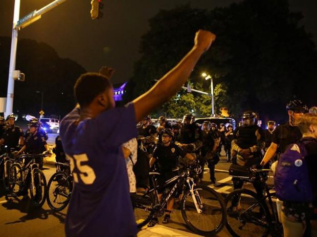Policiais e manifestantes são fotografados durante protesto em Charlotte, na Carolina do Norte, no domingo (25) (Foto: Mike Blake/Reuters)