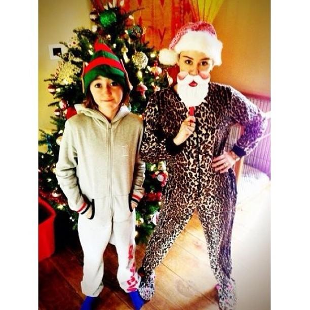 Miley Cyrus posa de macacão de oncinha e gorrinho de Papai Noel ao lado da irmã (Foto: Instagram)