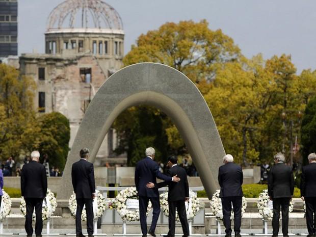 Secretário de Estados dos Estados Unidos, John Kerry, coloca o braço nas costas do ministro de relações exteriores do Japão, Fumio Kishida, durante uma visita ao Memorial de Hiroshima nesta segunda-feira (11). Cidade foi devastada por uma bomba americana  (Foto: Jonathan Ernst / AFP)