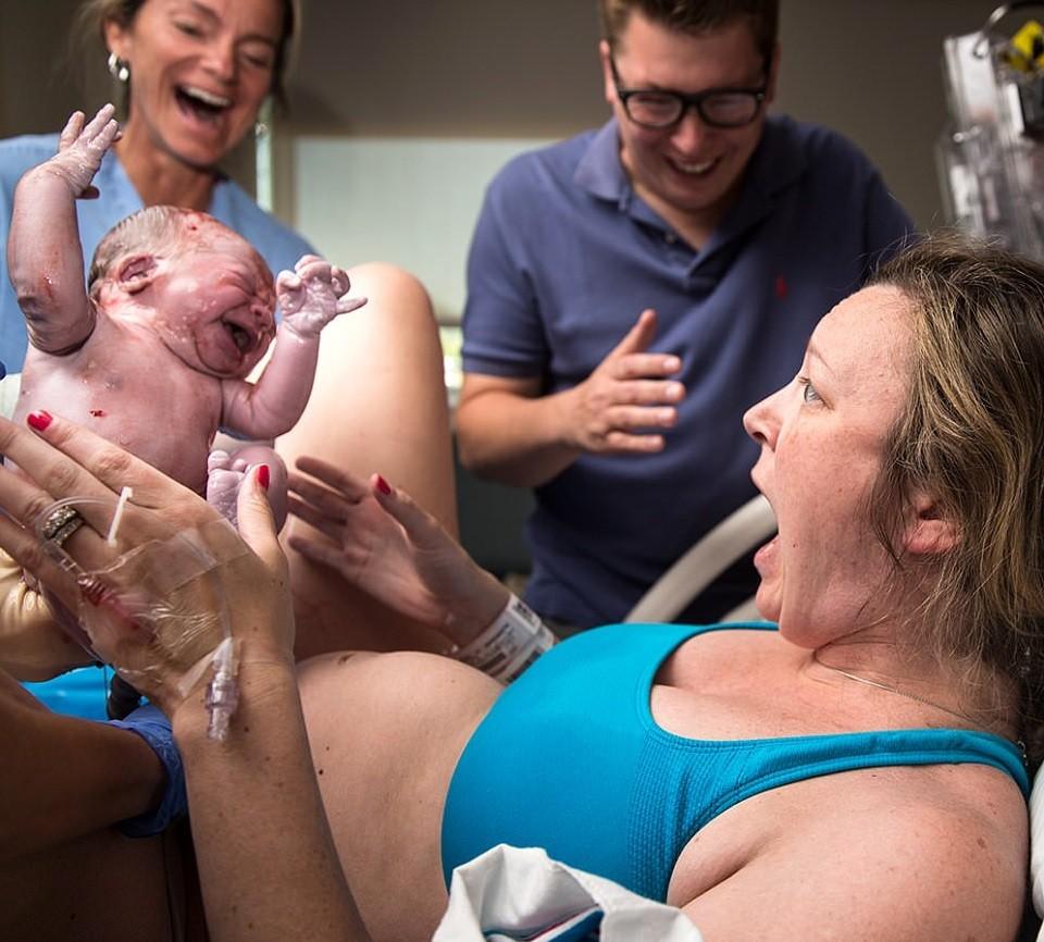 Dara fica surpresa ao ver o filho enquanto seu marido e a obstetriz comemoram ao fundo (Foto: Ker-Fox Fotografia)