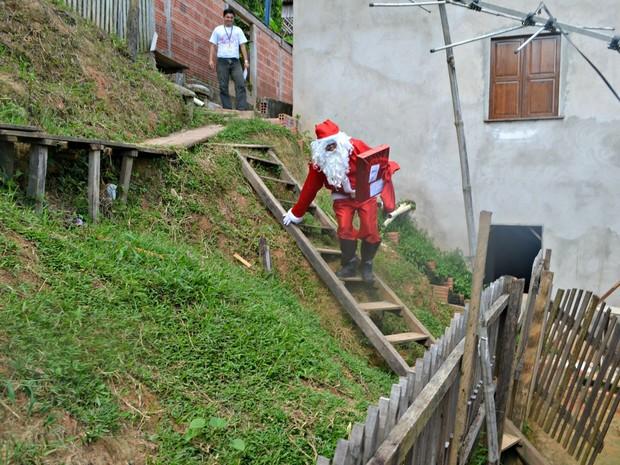 Papai Noel enfrenta locais de difícil acesso para cumprir a missão de entregar presentes em Cruzeiro do Sul  (Foto: Adelcimar Carvalho/G1)