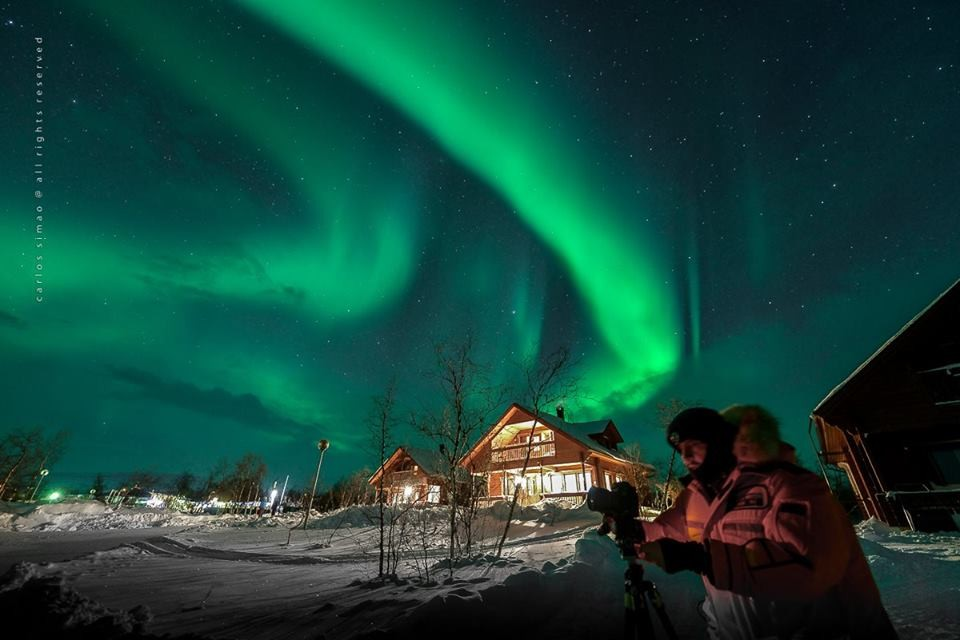 Marco prepara uma foto em meio à aurora em frente a um chalé no Ártico (Foto: Divulgação)