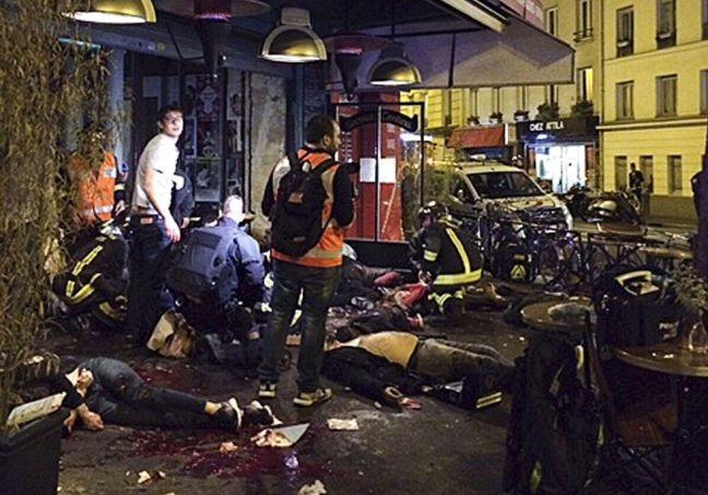 Vítimas atingidas por tiros na porta do restaurante La Bell Equipe (Foto: Anne Sophie Chaisemartin / AP)