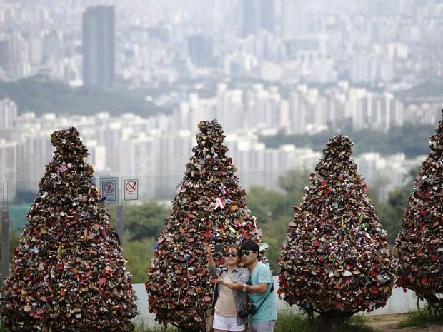 Casal na torre de Seul; árvores estão lotadas de cadeados do amor (Foto: Kim Hong-Ji/Reuters)