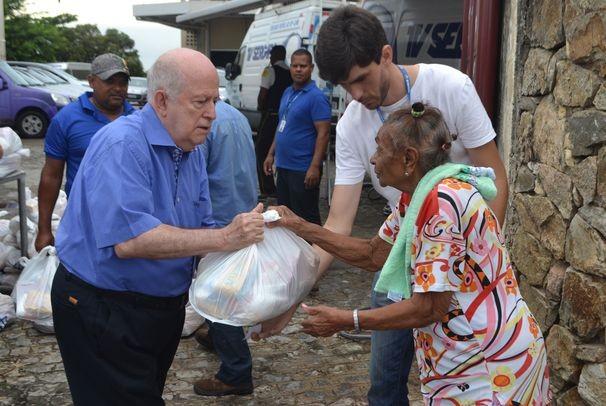 Diretor-presidente da TV Sergipe, Albano Franco, entrega cesta para moradora do Bairro Cidade Nova (Foto: Divulgação / TV Sergipe)