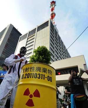 Manifestante vestido como trabalhador de usina batuca em tambor com logo de dejeto nuclear (Foto: AFP)