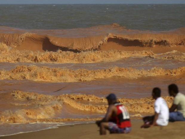 Homens observam uma onda de lama se quebrar na praia em Regência, no Espírito Santo. O local foi atingido pela lama após o rompimento de barragens de rejeitos da mineradora Samarco, cujos donos são a Vale e a australiana BHP, levada pelo Rio Doce  (Foto: Ricardo Moraes/Reuters)