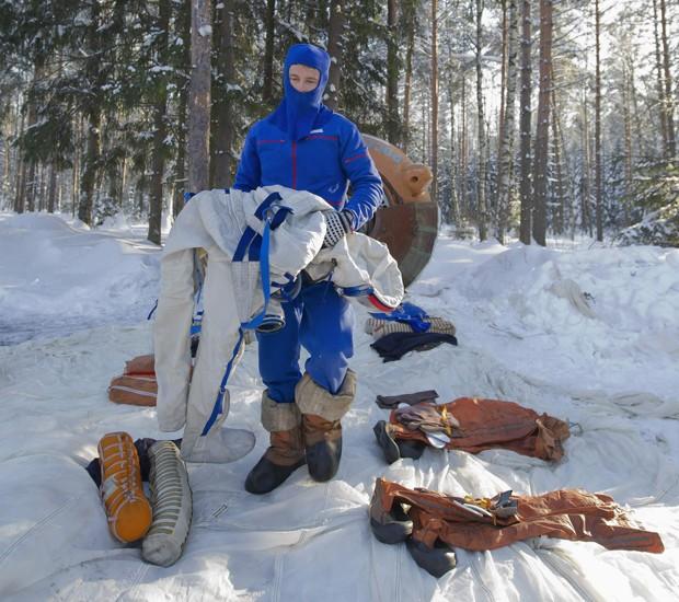 O astronauta americano Gregory Wiseman carrega roupas e equipamentos usados em treinamento em base russa, nesta quarta-feira (23) (Foto: Sergei Remezov/Reuters)