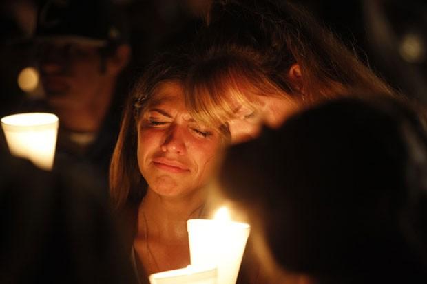 Mulheres se abraçam lamentando a morte de conhecidos na faculdade Umpqua, em vigília no Oregon (Foto: Steve Dipaola/Reuters)