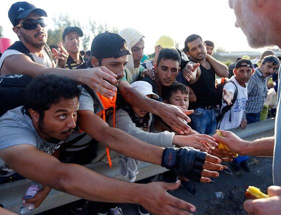 Imigrantes lutam por comida durante a saída de Budapeste. Impedidos de embarcar de trem, milhares de refugiados seguiram para a Áustria a pé (Foto: AP Photo/Frank Augstein)