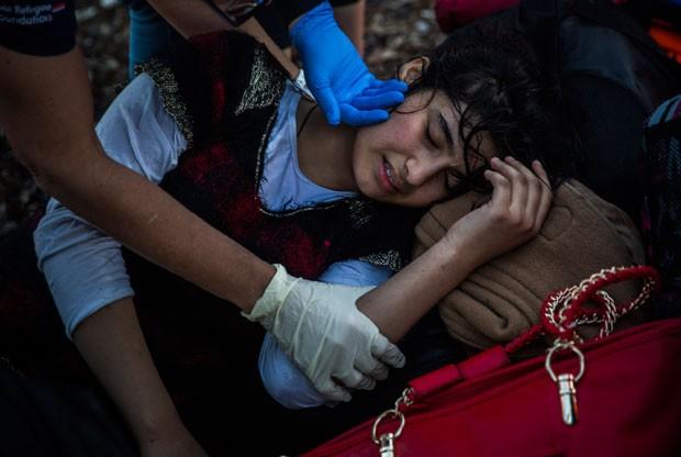Voluntários ajudam uma mulher exausta após a travessia do Mediterrâneo até a ilha de Lesbos (Foto: Santi Palacios/AP)