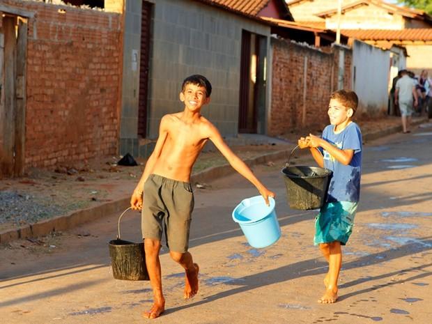 Crianças carregam baldes com a água que chegou em caminhão pipa (Foto: Geraldo Humberto / Inter TV)