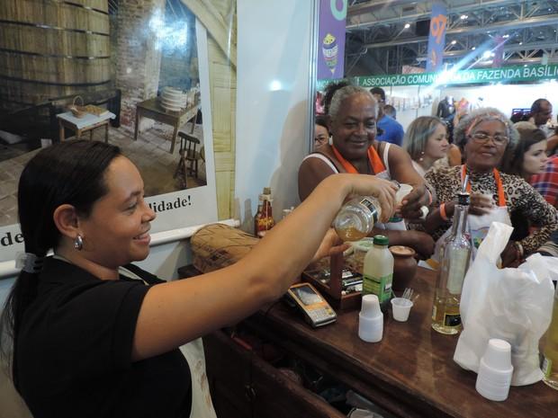 Vendedora oferece degustação de licores para feirantes (Foto: Moema França/G1)