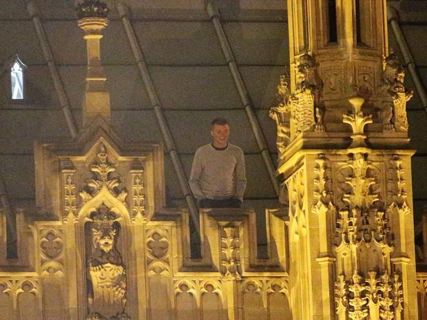 Foto tirada neste sábado (7) mostra jovem de 23 anos no telhado do Parlamento, em Londres (Foto: Yui Mok/PA Wire/AP)