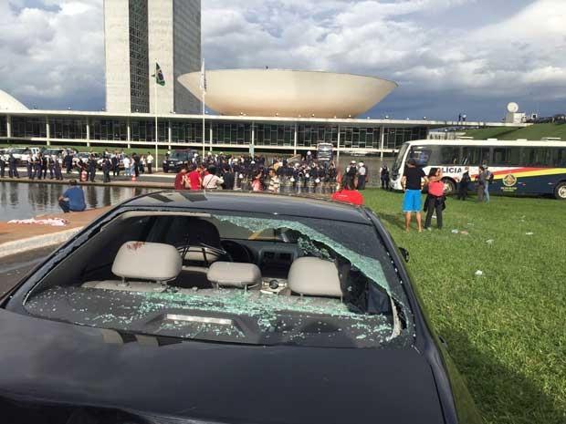 Carro estacionado próximo ao Congresso teve vidro quebrado durante protesto (Foto: Lucas Salomão / G1)