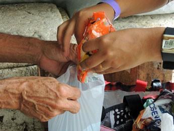 Antes de entrar, estudante transfere sabão em pó de embalagem (Foto: Katherine Coutinho / G1)
