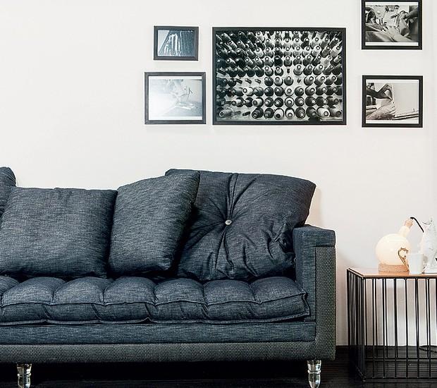 Com finas grades, essa mesa lateral causa um belo efeito na sala. O preto deste ambiente dá o contraste nas paredes brancas, junto com os quadros, deixando o visual clean e moderno (Foto: Ilana Bar/Editora Globo)