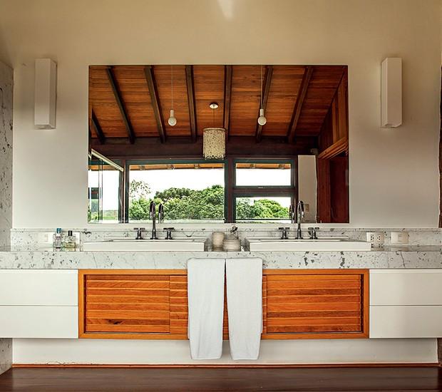 O arquiteto René Fernandes desenhou a bancada de mármore Carrara com duas cubas de sobrepor. O gabinete tem portas de madeira natural e gavetas de laca (Foto: Edu Castello/Casa e Jardim)
