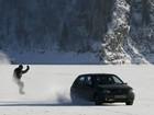 Russo pratica snowboard puxado por carro na superfície congelada de rio