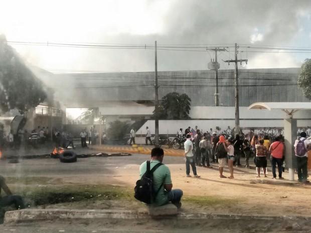 Manifestantes tocaram fogo em pneus no portão da garagem de uma empresa de ônibus de João Pessoa (Foto: André Resende/G1)