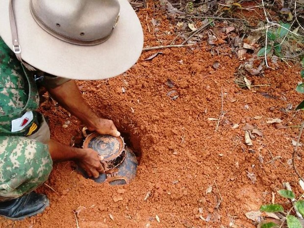 Policial desenterra recipiente com droga na zona rural de Abaeté (Foto: PM/Divulgação)