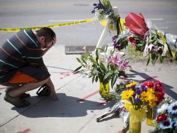 Homem se emociona diante de flores deixadas no limite estabelecido pela polícia perto da Igreja Emanuel AME, em homenagem às vítimas do tiroteio no bairro de maioria negra em Charleston (Foto: David Goldman/AP)