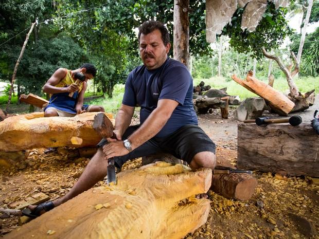 André da Marinheira talha madeira que se tranformará em um banco encomendado por um cleinte do Piauí. (Foto: Jonathan Lins/G1)