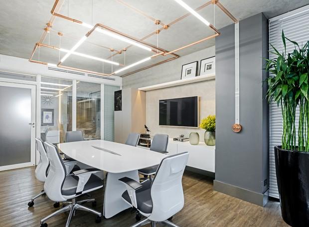 A sala de reunião tem rack e armários desenhados pela equipe Elmor Arquitetura. Mesa e cadeiras da Tecnoflex. Vaso à venda na Casa das Plantas (Foto: Rodrigo Ramirez/Divulgação)