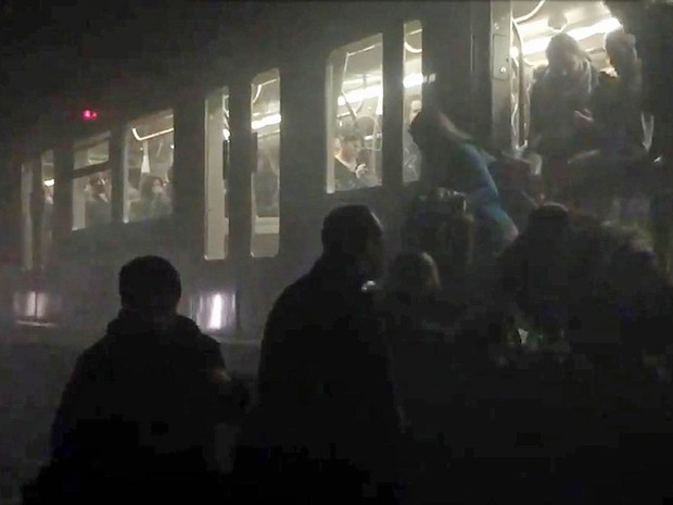 Passageiros deixam vagão do metrô e descem aos trilhos após explosão em estação de Bruxelas (Foto: Evan Lamos/EurActiv/AFP)