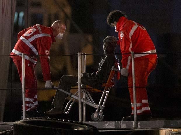 Sobrevivente é transportado em cadeira ao desembarcar de barco da guarda costeira italiana no porto de Catania na noite desta segunda-feira (20) (Foto: AP Photo/Alessandra Tarantino)