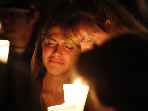 Mulheres se abraçam lamentando a morte de conhecidos na faculdade Umpqua, em vigília no Oregon, na madrugada após o tiroteio que deixou 10 mortos no campus (Foto: Steve Dipaola/Reuters)