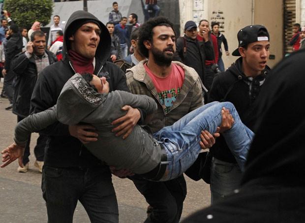 Manifestantes ajudam ferido após pessoas pró-governo jogarem pedra em opositores no Cairo (Foto: Asmaa Waguih/Reuters)
