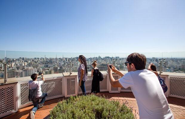Jovem tira fotografia com smartphone no topo do Edifício Itália, em São Paulo. (Foto: Divulgação/Ericsson)
