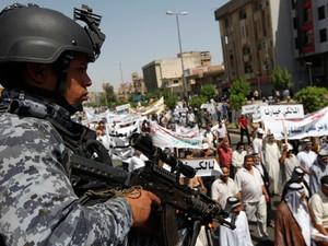 Um oficial da polícia iraquiana fica de guarda durante uma manifestação em apoio a primeiro-ministro iraquiano, Nuri al-Maliki, em Bagdá (Foto: Reuters)