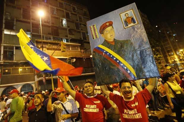 Chavistas reúnem-se em frente ao palácio de Miraflores, em Caracas, celebrando antecipadamente a vitória nas eleições deste domingo (7) (Foto: AP)