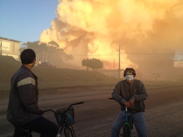 Moradores com máscaras observam fumaça em São Francisco do Sul (Foto: Emanuel Soares/CBN)