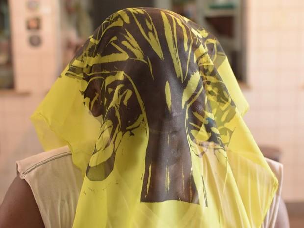"""Seo João, mestre artesão do Porto Vasconcelos, com o rosto coberto pela gravura criada por Bôscolo: """"homem tigre"""" (Foto: Ulysses Bôscolo)"""