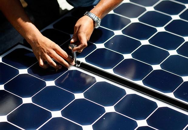 Painéis de energia solar sendo instalado em teto de residência (Foto: Joe Raedle/ Getty Images)