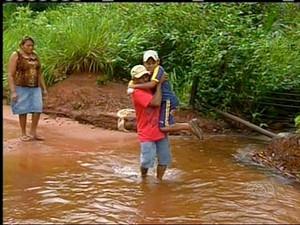 Lavrador de 71 anos tem que carregar os netos para atravessar córrego, em Araguaína (Foto: Reprodução/TV Anhanguera)